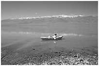 Kayaker near shore in Manly Lake. Death Valley National Park, California, USA. (black and white)