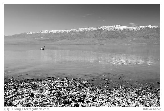 Salt formations, kayaker in a distance, and Panamint range. Death Valley National Park (black and white)