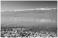Salt formations, kayaker in a distance, and Panamint range. Death Valley National Park ( black and white)