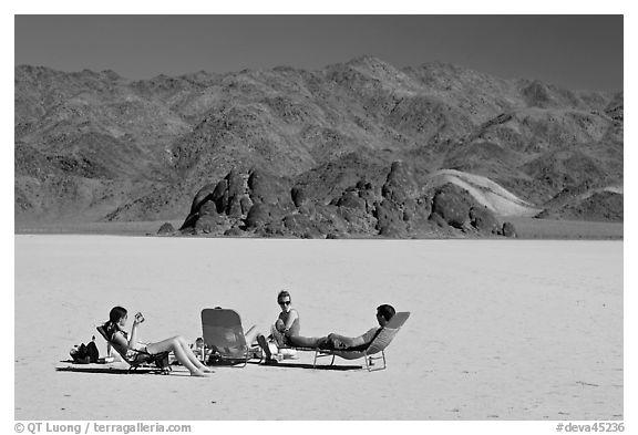 Tourists sunning themselves with beach chairs on the Racetrack. Death Valley National Park (black and white)