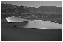 Hiker on ridge, Mesquite Dunes, sunrise. Death Valley National Park ( black and white)