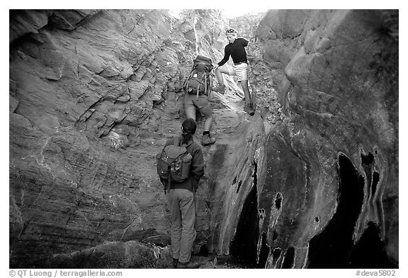 Hikers climbing in a narrow side canyon. Death Valley National Park (black and white)