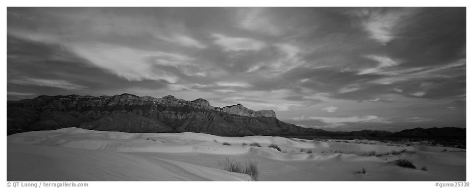 White sand dunes, mountain range, and colorful clouds. Guadalupe Mountains National Park (black and white)