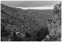 Cliffs and forested slopes, approaching storm. Guadalupe Mountains National Park, Texas, USA. (black and white)
