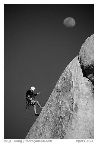 Climber rappelling down with moon. Joshua Tree National Park, California, USA.