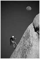 Climber rappelling down with moon. Joshua Tree National Park, California, USA. (black and white)
