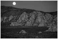 Moon rising about mountains. Joshua Tree National Park ( black and white)
