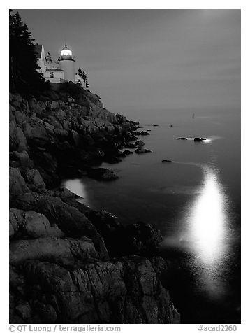 Bass Harbor lighthouse by night with reflections of moon and lighthouse light. Acadia National Park (black and white)