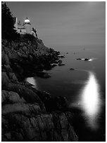 Bass Harbor lighthouse by night with reflections of moon and lighthouse light. Acadia National Park, Maine, USA. (black and white)