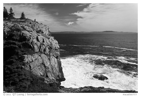 Tall granite sea cliff with person standing on top. Acadia National Park (black and white)