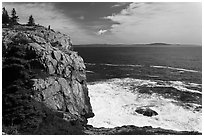 Tall granite sea cliff with person standing on top. Acadia National Park, Maine, USA. (black and white)
