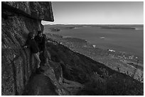 Hikers resting on ledge with handrails. Acadia National Park ( black and white)