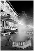 Fountain with thermal steam outside Fordyce Bath at night. Hot Springs National Park, Arkansas, USA. (black and white)