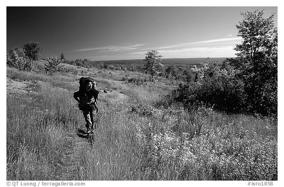 Backpacker walking on Greenstone ridge trail. Isle Royale National Park (black and white)