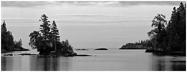 Tree-covered islet at dawn. Isle Royale National Park (Panoramic black and white)