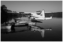 Pilot opening door at floatplane dock. Isle Royale National Park ( black and white)