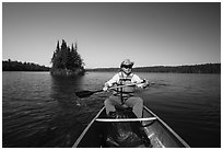 Canoist paddling and islet, Tobin Harbor. Isle Royale National Park ( black and white)