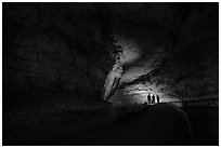 Family backlighted in dark cave corridor. Mammoth Cave National Park ( black and white)