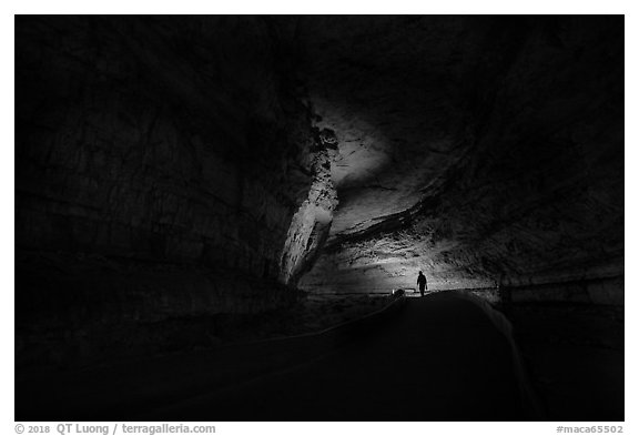 Ranger with lantern backlighted in dark cave corridor. Mammoth Cave National Park (black and white)