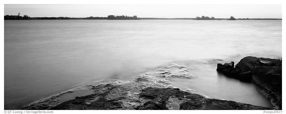 Lakeshore and glassy water painted yellow by sunrise. Voyageurs National Park (black and white)