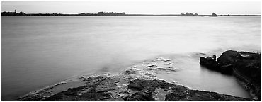 Lakeshore and glassy water painted yellow by sunrise. Voyageurs National Park (Panoramic black and white)