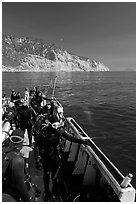 Divers in full wetsuits on diving boat, Santa Cruz Island. Channel Islands National Park, California, USA. (black and white)