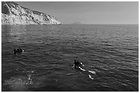 Scuba divers on ocean surface, Santa Cruz Island. Channel Islands National Park, California, USA. (black and white)