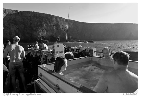 Divers relaxing in hot tub aboard the Spectre and Annacapa Island. Channel Islands National Park (black and white)