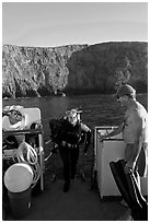 Woman diver stepping onto boat and Annacapa Island. Channel Islands National Park, California, USA. (black and white)