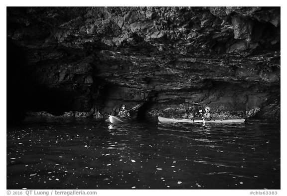 Two kayakers in sea cave with low ceiling, Santa Cruz Island. Channel Islands National Park (black and white)