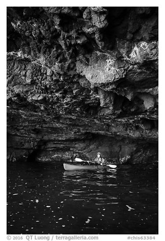 Kayaker in sea cave with low ceiling, Santa Cruz Island. Channel Islands National Park (black and white)
