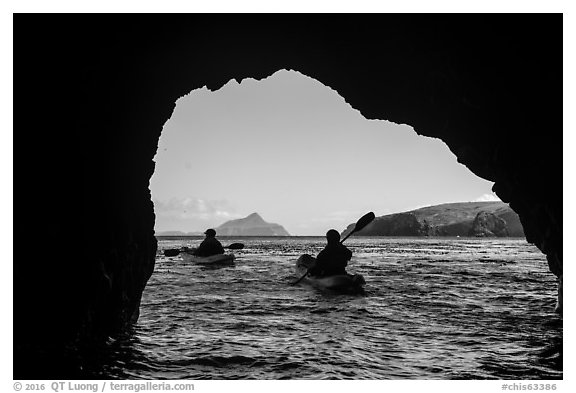 Kayakers exiting sea cave with West Anacapa in the distance, Santa Cruz Island. Channel Islands National Park (black and white)