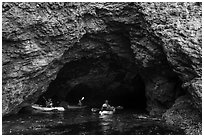 Kayakers at the entrance of sea cave, Santa Cruz Island. Channel Islands National Park ( black and white)