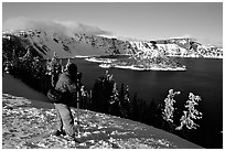 Photographer on  rim of  Lake in winter. Crater Lake National Park, Oregon, USA. (black and white)