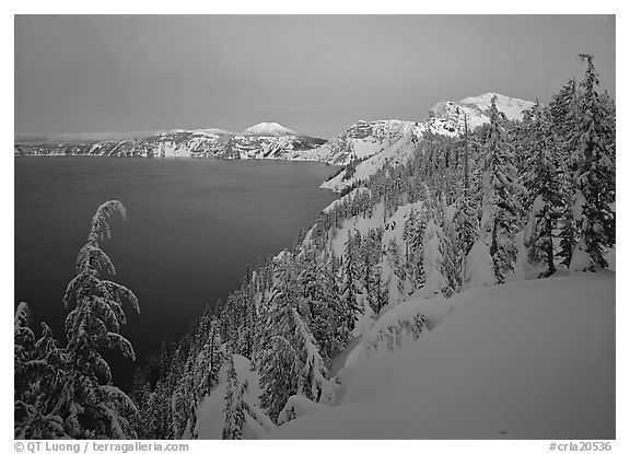 Snow-covered rim and trees, lake and mountains, dusk. Crater Lake National Park (black and white)