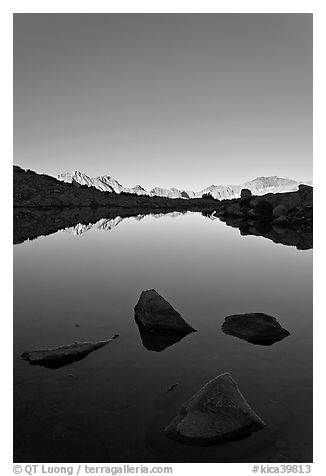 Rocks and calm lake with mountain reflections, early morning, Dusy Basin. Kings Canyon National Park (black and white)