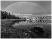 Rainbow in dark sky above Juniper Lake. Lassen Volcanic National Park ( black and white)
