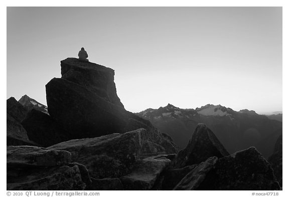 Man sitting on rock contemplates mountains at sunrise, North Cascades National Park.  (black and white)
