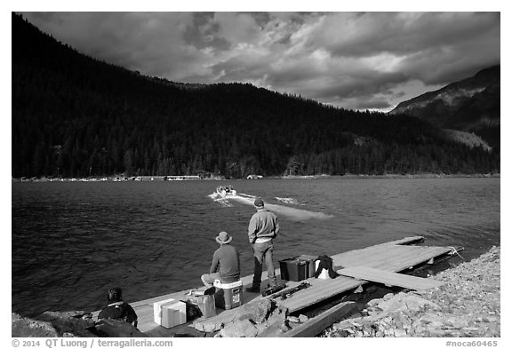 Guests waiting for ride across lake to Ross Lake resort, North Cascades National Park Service Complex.  (black and white)