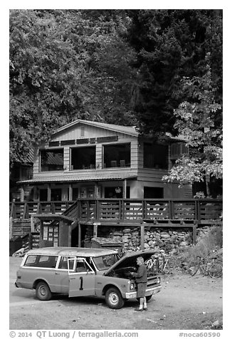 Man fixing old car in front of North Cascades Lodge, Stehekin, North Cascades National Park Service Complex.  (black and white)