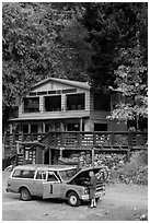 Man fixing old car in front of North Cascades Lodge, Stehekin, North Cascades National Park Service Complex.  ( black and white)