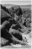 Hikers approaching cliff with steps carved in stone. Pinnacles National Park ( black and white)
