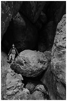 Man with headlamp looking up in Balconies Cave. Pinnacles National Park, California, USA. (black and white)