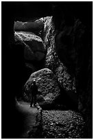 Hiker with headlamp in Bear Gulch Cave. Pinnacles National Park ( black and white)