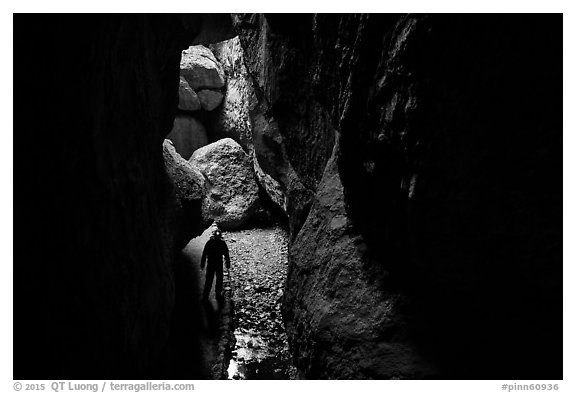 Hiker with lamp in Bear Gulch Cave. Pinnacles National Park (black and white)