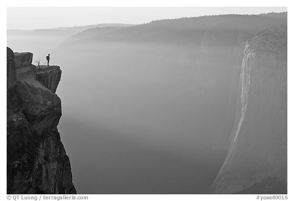 Hiker standing on top of sheer cliff at Taft point. Yosemite National Park (black and white)