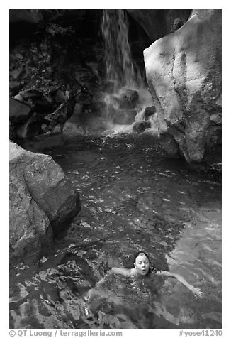 Girl swims in cool pool at the base of Wapama falls. Yosemite National Park (black and white)