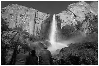 Tourists looking at Bridalvail Fall rainbow. Yosemite National Park, California, USA. (black and white)