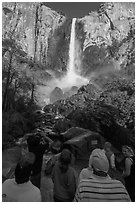 Tourists standing below Bridalvail Fall. Yosemite National Park, California, USA. (black and white)