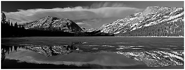 Mountains reflected in partly iced Tenaya Lake. Yosemite National Park (Panoramic black and white)